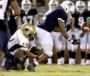 Photo - Heritage Hall's Chedon Shockley, left, tackles Casady's Cassius Calhoun as Calhoun loses control of the ball during a 2010 game at Casady. Photo by Bryan Terry, The Oklahoman Archives
