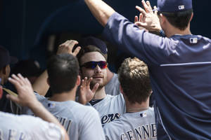 Photo - Milwaukee Brewers Jonathan Lucroy, center, celebrates after scoring on a single by Carlos Gomez during first inning interleague baseball action against the Toronto Blue Jays in Toronto on Wednesday July 2 , 2014. (AP Photo/The Canadian Press, Chris Young)