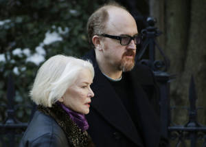 Photo - Ellen Burstyn and Louis C.K. arrive for the funeral of actor Philip Seymour Hoffman at the Church of St. Ignatius Loyola, Friday, Feb. 7, 2014 in New York. Hoffman, 46, was found dead Sunday of an apparent heroin overdose. (AP Photo/Mark Lennihan)