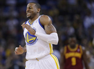Photo - Golden State Warriors' Andre Iguodala smiles after making a three-point basket against the Cleveland Cavaliers during the first half of an NBA basketball game on Friday, March 14, 2014, in Oakland, Calif. (AP Photo/Marcio Jose Sanchez)