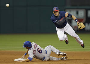 Photo - Cleveland Indians shortstop Asdrubal Cabrera throws over New York Mets' Matt den Dekker (6) to complete a double play on Mets' Omar Quintanilla in the fifth inning of a baseball game Saturday, Sept. 7, 2013, in Cleveland. (AP Photo/Mark Duncan)