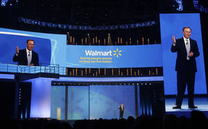 Photo -   Mike Duke, President and CEO of Wal-Mart, center, speaks to shareholders as his image appears on screens left and right in Fayetteville, Ark., Friday, June 3, 2011. (AP Photo/Danny Johnston)