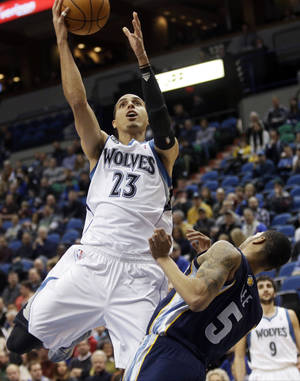 Photo - Minnesota Timberwolves' Corey Brewer lays up a basket as Memphis Grizzlies' Courtney Lee falls backward in the first quarter of an NBA basketball game on Friday, Jan. 31, 2014, in Minneapolis. (AP Photo/Jim Mone)