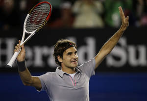 Photo - Switzerland's Roger Federer reacts after defeating Australia's Bernard Tomic in their third round match at the Australian Open tennis championship in Melbourne, Australia, Saturday, Jan. 19, 2013. (AP Photo/Andy Wong)