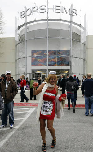 Photo - Karma Perrot of New Mexico arrives at a reception for Berkshire Hathaway shareholders dressed as a Heinz Ketchup bottle at the Borsheims jewelry store in Omaha, Neb., Friday, May 3, 2013. Heinz was recently acquired by Berkshire Hathaway.  More than 30,000 people are expected to attend Saturday's Berkshire Hathaway shareholder meeting to hear Warren Buffett and Charlie Munger answer questions for more than six hours. No other annual meeting can rival Berkshire's, which is known for its size, the straight talk Buffett and Munger offer and the sales records shareholders set while buying Berkshire products. (AP Photo/Nati Harnik)