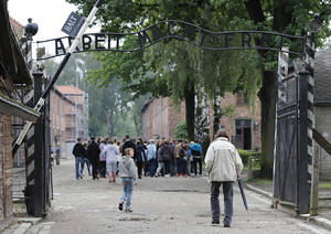 Photo - FILE- Tourists visit the former Nazi death camp of Auschwitz in Oswiecim, Poland, in this file photo dated Wednesday, June 6, 2012.  The Auschwitz-Birkenau memorial site in southern Poland registered 1.43 million visitors last year, a record number in its 65-year history as a place of Holocaust remembrance, officials said Friday Jan 4, 2013. (AP Photo/Gregorio Borgia, File)