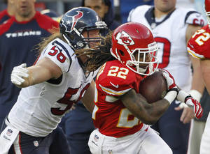 Photo - Kansas City Chiefs wide receiver Dexter McCluster (22) is tackled by Houston Texans inside linebacker Brian Cushing (56) during the second half of an NFL football game at Arrowhead Stadium in Kansas City, Mo., Sunday, Oct. 20, 2013. (AP Photo/Colin E. Braley)