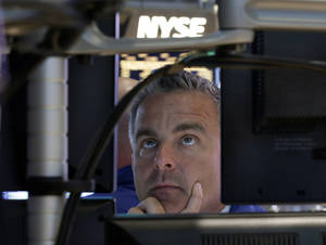 Photo - In this Wednesday, Sept. 18, 2013, photo, specialist Christopher Culhane works at his post on the floor of the New York Stock Exchange after the Federal Reserve announcement. Global stock markets surged Thursday after the U.S. Federal Reserve unexpectedly refrained from reducing its massive economic stimulus.  (AP Photo/Richard Drew)