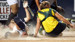 Photo - Kaitlin Cochran of the USA slides past Australian catcher Tracey Mosley without touching home base during the championship game Monday.  Photo By Ashley McKee, The Oklahoman