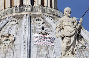 "Photo -   Firefighters look at Italian businessman Marcello di Finizio standing above his banner which reads in Italian ""Help!! Enough Monti (Italian Premier Mario Monti), enough Europe, enough multinationals, you are killing all of us. Development?? This is a social butchery!!"", as he protests on St. Peter's 130-meter-high (42-feet-high) dome, at the Vatican, Wednesday, Oct. 3, 2012. An Italian man has eluded Vatican security and scaled the 130-meter-high (42-feet-high) dome of St. Peter's Basilica to protest Italian government and European Union policies. Officials said Wednesday that the man, who identified himself as the owner of a beach resort, refused appeals from government ministers offering to meet with him if he would come down. (AP Photo/Andrew Medichini)"