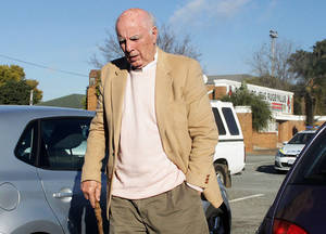 Photo - Bob Hewitt, the former Grand Slam doubles champion and one-time tennis hall of famer, is seen outside the magistrates court in Boksburg, South Africa, Friday, June 6, 2014. The lawyer representing Bob Hewitt says he has been charged with rape and sexual assault of minors and will go to trial in February. Attorney Alwyn Griebenow told The Associated Press that Hewitt denies two charges of rape and one of sexual assault of girls he coached in South Africa decades ago. Griebenow said Hewitt attended Boksburg Magistrate's Court near Johannesburg on Friday and told the court he understood the charges. He was not asked to enter a plea, but Griebenow said he would plead not guilty to all three charges at his trial. The Australian-born Hewitt, now 74, won nine grand slam doubles and six mixed doubles titles in the 1960s and 1970s.(AP Photo/Nokuthula Mbatha - The Star)     SOUTH AFRICA OUT