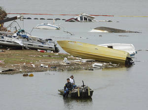 Photo - A salvage diver moves into position to recover boats and debris at Lake Thunderbird on Wednesday, May 12, 2010, in Norman, Okla., from the storms that hit the area Monday. (AP Photo/The Oklahoman, Steve Sisney)