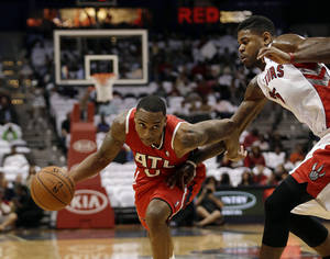 Photo - Atlanta Hawks point guard Jeff Teague (0) drives against Toronto Raptors point guard Kyle Lowry (7) in the first half of an NBA basketball game Friday, Nov. 1, 2013, in Atlanta. (AP Photo/John Bazemore)