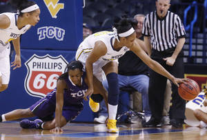 Photo - West Virginia center Asya Bussie (20) reaches over TCU guard Zahna Medley (14) for a loose ball in the first half of an NCAA college basketball game in the quarterfinals of the Big 12 Conference women's tournament in Oklahoma City, Saturday, March 8, 2014.  (AP Photo/Sue Ogrocki)