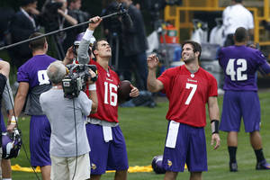 Photo - Minnesota Vikings' quarterback Christian Ponder, center right, and quarterback Matt Cassel, center left, fool around with a microphone during their football practice at the Grove Hotel in Watford, England, Wednesday, Sept. 25, 2013. Vikings play Pittsburgh Steelers on Sunday in a NFL football game at Wembley Stadium in London. (AP Photo/Sang Tan)