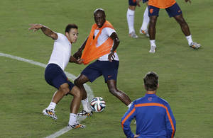 Photo - Netherlands' Memphis Depay, left, tackles Bruno Martins Indi, right, during their training session at the Roberto Santos stadium on Friday, July 4, 2014 in Salvador, Brazil. Netherlands play their quarterfinal match of the 2014 World Cup soccer tournament against Costa Rica on July 5 in Salvador.(AP Photo/Wong Maye-E)