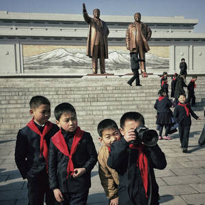 Photo - In this Feb. 16, 2013 photo taken with an iPhone and posted to Instagram on Feb. 16 , 2013, North Korean school boys play with an Associated Press photographer's professional camera in front of statues of the late leaders Kim Il Sung and Kim Jong Il, on Mansu Hill in Pyongyang, North Korea. On Jan. 18, 2013, foreigners were allowed for the first time to bring mobile phones into North Korea. And this week the local service provider, Koryolink, is allowing foreigners to access the Internet on a data capable 3G connection on mobile phones.(AP Photo/David Guttenfelder)