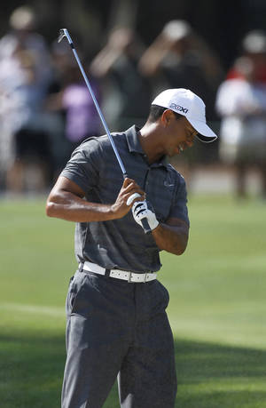 Photo -   Tiger Woods reacts to his shot from a 15th hole bunker during the first round of the Players Championship golf tournament, Thursday, May 10, 2012, at Sawgrass in Ponte Vedra, Fla. (AP Photo/Chris O'Meara)
