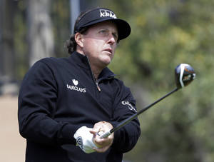 Photo - Phil Mickelson watches his tee shot as he takes part in a pro-am at the Valero Texas Open, Wednesday, March 26, 2014, in San Antonio. Mickelson is straying from his usual schedule and playing in the Valero Texas Open for the first time in 22 years. (AP Photo/Eric Gay)