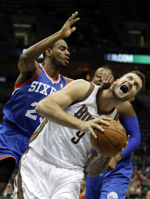 Photo - Milwaukee Bucks' Miroslav Raduljica (9) is fouled as he goes up for a shot against Philadelphia 76ers' Elliot Williams during the second half of an NBA basketball game Saturday, Dec. 21, 2013, in Milwaukee. (AP Photo/Morry Gash)