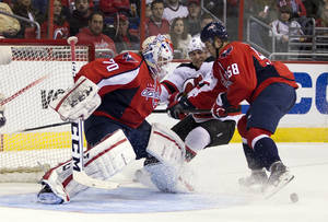 Photo - Washington Capitals goalie Braden Holtby, left, and defenseman Connor Carrick, right, battle New Jersey Devils right wing Stephen Gionta during the first period of an NHL hockey game on Saturday, Feb. 8, 2014, in Washington. (AP Photo/ Evan Vucci)