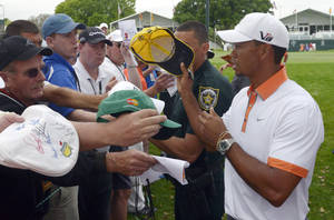 Photo - Tiger Woods, right, signs autographs for fans after finishing his weather-shortened round on the ninth green of the pro-am of the Arnold Palmer Invitational golf tournament in Orlando, Fla., Wednesday, March 20, 2013.(AP Photo/Phelan M. Ebenhack)