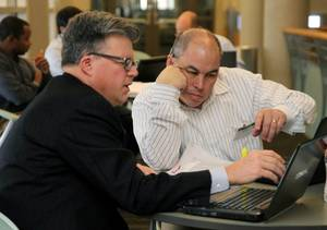 photo - Donald Rowlett and Durand Crosby collaborate Thursday in the Ph.D. in Business for Executives program at OSU-Tulsa.?STEPHEN PINGRY/Tulsa World   <strong></strong>