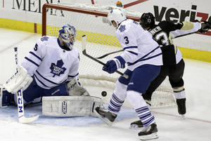 Photo - Pittsburgh Penguins right wing Chris Conner (23) gets the puck behind Toronto Maple Leafs goalie Jonathan Bernier (45) and Dion Phaneuf (3) for a goal in the first period of an NHL hockey game, Monday, Dec. 16, 2013, in Pittsburgh. (AP Photo/Gene J. Puskar)