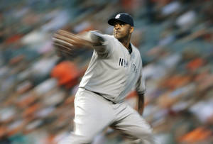 Photo - In this photo made with a slow shutter speed, New York Yankees starting pitcher CC Sabathia throws to the Baltimore Orioles in the fourth inning of a baseball game in Baltimore, Monday, May 20, 2013. (AP Photo/Patrick Semansky)