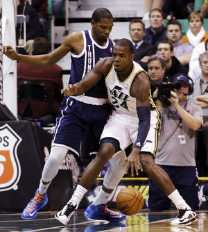Photo - Oklahoma City Thunder's Kevin Durant, left, defends against Utah Jazz's Paul Millsap (24) in the first quarter of an NBA basketball game, Tuesday, Feb. 12, 2013, in Salt Lake City. (AP Photo/Rick Bowmer) ORG XMIT: UTRB106