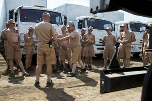 Photo - Drivers listen to instructions as they stand near their  white trucks with humanitarian aid after parking in a field about 28 kilometers from Ukrainian border in Rostov-on-Don region, Russia, Thursday, Aug. 14, 2014. Russia on Tuesday dispatched some hundreds of trucks, although only a small proportion were counted in this convoy, covered in white tarps on a mission to deliver aid to a rebel-held zone in eastern Ukraine. (AP Photo/Pavel Golovkin)