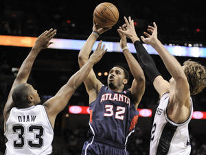 photo -   Atlanta Hawks' Mike Scott (32) shoots over San Antonio Spurs' Boris Diaw (33), of France, and Tiago Splitter, of Brazil, during the second half of an NBA preseason basketball game, Wednesday, Oct. 10, 2012, in San Antonio. San Antonio won 101-99. (AP Photo/Darren Abate)