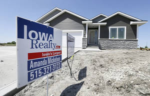Photo - In this May 21, 2014 photo, a sign sits in front of a new home for sale in West Des Moines, Iowa.  The Commerce Department reports on sales of new homes in April on Friday, May 23, 2014. (AP Photo/Charlie Neibergall)