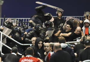Photo - Hungarian fans clash with Romanian riot police before the 2014 World Cup Group D qualifying soccer match between Romania and Hungary at the National Arena stadium in Bucharest, Romania, Friday Sept. 6, 2013. (AP Photo/Vadim Ghirda)