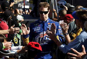 Photo -   Brad Keselowski high-fives fans prior to a NASCAR Sprint Cup Series auto race at Phoenix International Raceway, Sunday, Nov. 11, 2012, in Avondale, Ariz. (AP Photo/Ross D. Franklin)