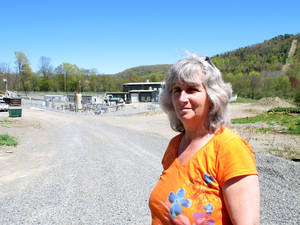 Photo - FILE - In this Monday, May 6, 2013, file photo, Vera Scroggins stands in front of a gas compressor station in Liberty Township in northwestern Pennsylvania. Scroggins, a  high-profile anti-fracking activist who often gives tours of natural gas drilling sites in northeastern Pennsylvania's Marcellus Shale region, asked a judge Monday, March 24, 2014, for relief from an order barring her from stepping foot on more than 300 square miles of land owned or leased by one of the state's leading natural gas drillers. Scroggins said the injunction, in place since October, has effectively prevented her from traveling to her favorite grocery store, eye doctor, hospital, restaurants, businesses and friends' homes because all of them have leased land to Cabot Oil & Gas Corp. (AP Photo/Mary Esch, File)