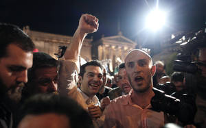 Photo -   Left Coalition party leader Alexis Tsipras greets supporters with a clenched fist, in central Athens after elections on Sunday, May 6, 2012. Tsipras was projected to come second in the poll, behind the front-runner conservatives, on a pledge to cancel Greece's bailout agreements. (AP Photo/Kostas Tsironis)