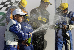 photo - Driver Scott Pruett, front left, sprays other drivers including Marco Ambrose, center, of Australia, in Victory Lane after winning the Grand-Am Series Rolex 24 hour auto race at Daytona International Speedway, Sunday, Jan. 27, 2013, in Daytona Beach, Fla. (AP Photo/John Raoux)