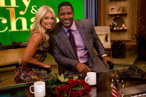 "Photo -   Former football player Michael Strahan, right, poses Kelly Ripa on the set of the newly named ""Live! with Kelly and Michael"" on Tuesday, Sept. 4, 2012 in New York. Strahan joined the popular morning show as a permanent co-host on Tuesday, fulfilling a joking prophecy he made to Regis Philbin more than four years ago. The gap-toothed former New York Giant jogged onto the morning show set and picked up co-host Kelly Ripa in a bear hug, lifting her off her feet. He replaces Philbin, who left last November. Strahan was the survivor in a series of on-air tryouts of potential co-hosts since Philbin left, and his hiring has been an open secret for the past two weeks. (Photo by Charles Sykes/Invision/AP Images)"