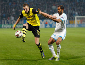 Photo - Dortmund's Kevin Grosskreutz, left, controls the ball while Marseille's Saber Khalifa looks on during the Group F Champions League soccer match between Olympique Marseille and Borussia Dortmund at the Velodrome stadium in Marseille, Southern France, Wednesday, Dec. 11, 2013. (AP Photo/Claude Paris)