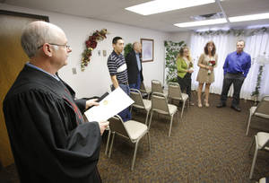 photo - Jerry Freeland, left,  officiates the wedding service for Tammie and Roger Lockwood at the Courthouse Lab & Wedding Chapel in Oklahoma City, Wednesday December 12, 2012. Dozens of couples decided to Tie The Knot on 12-12-12. Photo By Steve Gooch, The Oklahoman