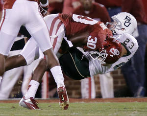 Photo - Oklahoma's Javon Harris (30) brings down Baylor's Clay Fuller (23) during the college football game between the University of Oklahoma Sooners (OU) and Baylor University Bears (BU) at Gaylord Family - Oklahoma Memorial Stadium on Saturday, Nov. 10, 2012, in Norman, Okla.  Photo by Chris Landsberger, The Oklahoman
