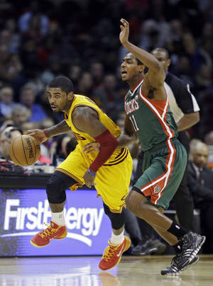 Photo - Cleveland Cavaliers' Kyrie Irving, left, dribbles past Milwaukee Bucks' Brandon Knight (11) during the first quarter of an NBA basketball game Friday, Dec. 20, 2013, in Cleveland. (AP Photo/Mark Duncan)