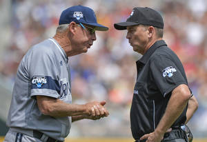 Photo - UC Irvine coach Mike Gillespie, left, has words with first base umpire Doug Williams after UC Irvine's Connor Spencer grounded out to Texas' shortstop C.J Hinojosa, in the third inning of an NCAA baseball College World Series game in Omaha, Neb., Saturday, June 14, 2014. (AP Photo/Ted Kirk)