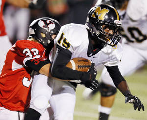 Photo - Yukon's Bradyn Meyer (30) tackles Anthony Barclay (19) of Midwest City during a high school football game between Yukon and Midwest City in Yukon, Okla., Thursday, Oct. 24, 2013. Photo by Nate Billings, The Oklahoman