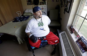 Photo - In a Thursday, June 19, 2014 photo, Brent Kaderli, a 30-year-old quadriplegic, sits in his room at the Baywood Crossing Rehabilitation and Healthcare Center, in Pasadena, Texas. Kaderli said Medicaid approved him for only three hours of at-home daily care, but he'd need at least six to get by while his father is at work. So he lives in a nursing home in Pasadena, Texas instead of at his father's house with help from aides. (AP Photo/David J. Phillip)