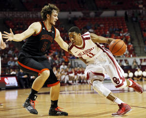 Photo - Oklahoma's Isaiah Cousins (11) drives the ball against Mercer's Bud Thomas (5) during an NCAA men's college basketball game between the Oklahoma Sooners (OU) and the Mercer Bears at Lloyd Noble Center in Norman, Okla., Monday, Dec. 2, 2013. Photo by Nate Billings, The Oklahoman