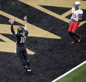Photo - Wake Forest's Tanner Price (10) celebrates after catching a touchdown pass as Maryland's Sean Davis (21) watches during the first half of an NCAA college football game in Winston-Salem, N.C., Saturday, Oct. 19, 2013. (AP Photo/Chuck Burton)
