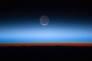 Photo - This undated image made available by NASA and photographed by the Expedition 28 crew aboard the International Space Station, shows the moon, at center with the limb of Earth near the bottom transitioning into the orange-colored troposphere, the lowest and most dense portion of the Earth's atmosphere.  A team of former NASA executives are launching a private venture to send people to the moon for $1.5 billion. The newly formed business is offering countries a two-person trip to the moon, either for research or national prestige. The venture was announced Wednesday, Dec. 6, 2012. (AP Photo/NASA)