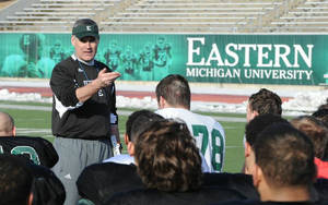 Photo - In an undated photo provided by Eastern Michigan University, head football coach Chris Creighton talks to his team in Ypsilanti, Mich. The new football coach wants his team to have the attitude that it will play anyone, anywhere. Creighton says the Eagles are so tough they would play on a parking lot. (AP Photo/Eastern Michigan University, HOPD)
